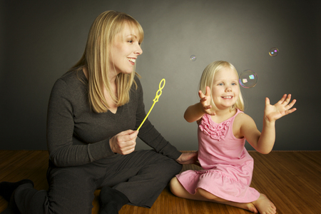 Rebecca and child playing with soap bubbles